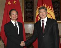 Китайский премьер Вэнь Цзябао (слева) жмет руку президенту Киргизии Алмазбеку Атамбаеву в резиденции под Бишкеком 4 декабря 2012 года. Китай согласился дать граничащей с ним Киргизии льготный кредит в $136 миллионов для реконструкции автодороги в Таджикистан, сказал премьер Киргизии Жанторо Сатыбалдиев. REUTERS/Vladimir Pirogov