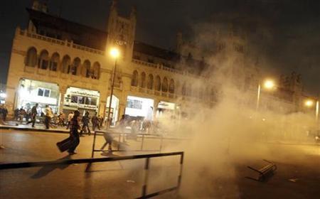 Anti-Mursi protesters run from smoke from a tear gas canister thrown by riot police, during clashes in front of the presidential palace in Cairo, December 4, 2012. REUTERS/Amr Abdallah Dalsh