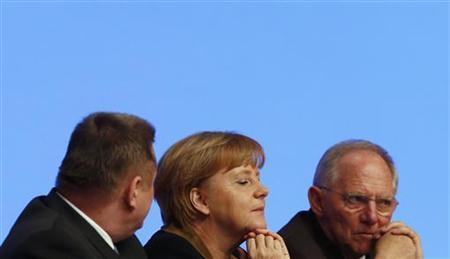 German Chancellor and leader of Germany's Christian Democratic Union (CDU) Angela Merkel (C) talks to party fellow and Finance Minister Wolfgang Schaeuble (R ) and party general Hermann Groehe (L) during the CDU's annual party meeting in Hanover, December 4, 2012. REUTERS/Kai Pfaffenbach