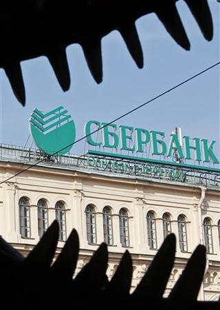 A Sberbank sign is on display on the roof of a building, with a dinosaur sculpture at a wax-figure museum seen in the foreground, in St. Petersburg September 19, 2012. REUTERS/Alexander Demianchuk