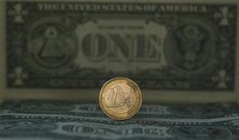 Монета 1 евро на фоне банкнот американского доллара в Мадриде 17 ноября 2011 года. Единая европейская валюта в начале европейской сессии среды достигла отметки $1,3127 - максимального значения с 18 октября, отыгрывая надежды на ослабление долгового кризиса еврозоны и связанное с этим сокращение ранее взятых коротких позиций в евро/доллар. REUTERS/Sergio Perez
