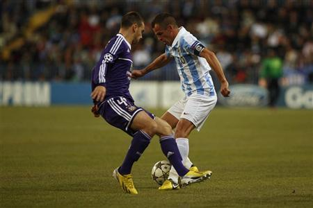 Malaga's Sergio Duda (R) fights for the ball Anderlecht's Massimo Bruno during their Champions League Group C soccer match at La Rosaleda stadium in Malaga, southern Spain December 4, 2012. REUTERS/Jon Nazca
