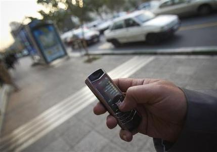 An Iranian man uses a mobile phone while standing on a street in northern Tehran October 24, 2010. Picture taken on October 24, 2010. To match Special Report IRAN-HUAWEI/ REUTERS/Morteza Nikoubazl/Files