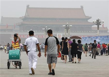 Visitors to Tiananmen Square shield themselves from the sun with umbrellas on a hot and hazy day in Beijing July 28, 2010. REUTERS/David Gray