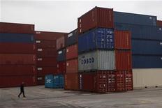 Homem anda em meio a containers de exportação no Porto de Xangai. O crescimento do setor de serviços da China desacelerou em novembro uma vez que o fraco avanço em novas encomendas e uma alta das contratações recentes reduziram os negócios pendentes. 10/11/2012 REUTER/Aly Song