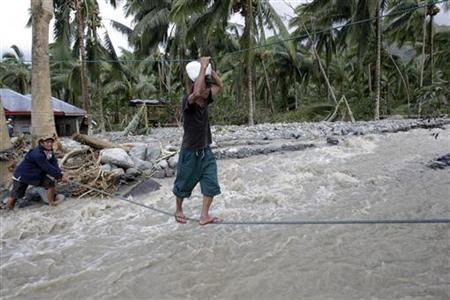A villager walks on rope over floodwaters that flows down a destroyed road caused by typhoon Bopha in Compostela Valley, southern Philippines December 5, 2012. REUTERS/Erik De Castro (PHILIPPINES - Tags: DISASTER ENVIRONMENT)