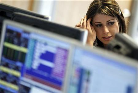 A dealer monitors her screens on the trading floor of IG Index in London May 6, 2010. REUTERS/Kevin Coombs/Files