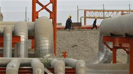 Workers, framed between insulated pipes, push a trolley at the Vadinar refinery, operated by Essar Oil Ltd., (EOL) in Gujarat June 5, 2012. REUTERS/Amit Dave/Files