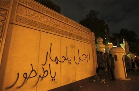 Anti-Mursi protesters gather near graffiti sprayed on the wall around the presidential palace in Cairo December 4, 2012. Egyptian police battled thousands of protesters outside President Mohamed Mursi's palace in Cairo on Tuesday, prompting the Islamist leader to leave the building, presidenty sources said. The words read, ''Go awaa donkey''. REUTERS/Amr Abdallah Dalsh (EGYPT - Tags: POLITICS CIVIL UNREST)