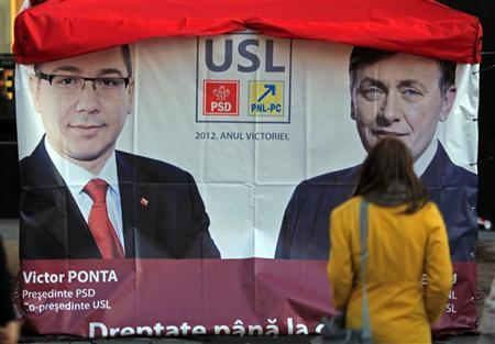 A woman walks past an election poster showing Social Liberal Union (USL) leaders, leftist Prime Minister Victor Ponta, the president of Social Democrat Party and Crin Antonescu, the president of National Liberal Party (R), in downtown Bucharest December 3, 2012. REUTERS/Radu Sigheti