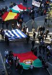 Демонстранты несут флаги Португалии, Греции, Испании и Италии во время митинга на афинской площади Синтагма 14 ноября 2012 года. Спад экономической активности в еврозоне был менее выражен в ноябре 2012 года, чем предполагалось ранее, хотя указаний на то, что регион выйдет из рецессии в скором времени, практически нет, свидетельствуют данные бизнес-обзоров. REUTERS/Yannis Behrakis