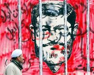 El vicepresidente egipcio dijo el miércoles que se pueden acordar y poner por escrito enmiendas a los artículos más polémicos del borrador de constitución antes del referéndum del 15 de diciembre, pidiendo un diálogo con la oposición para poner fin a una crisis. En la imagen, un hombre camina frente a un mural con el rostro del presidente egipcio, Mohamed Mursi, en el palacio presidencial de El Cairo, el 5 de diciembre de 2012. REUTERS/Amr Abdallah Dalsh
