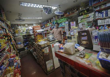 An employee weighs a packet chickpea flour inside a mom and pop grocery store at a residential area in Mumbai December 5, 2012. India's fragile ruling coalition won a vote on allowing foreign supermarkets to operate in Asia's third-largest economy in a test of support for Prime Minister Manmohan Singh's minority government and his flagship economic reform. REUTERS/Danish Siddiqui