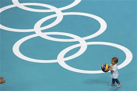 A child plays on the pitch after a volleyball match at Earls Court during the London 2012 Olympic Games August 12, 2012. REUTERS/Olivia Harris/Files