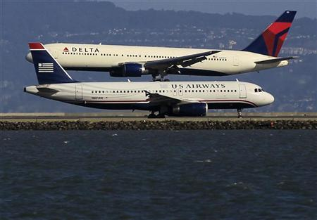 A Delta plane lands as a U.S. Airways plane waits to take off at San Francisco airport, California January 21, 2012. REUTERS/Lucy Nicholson