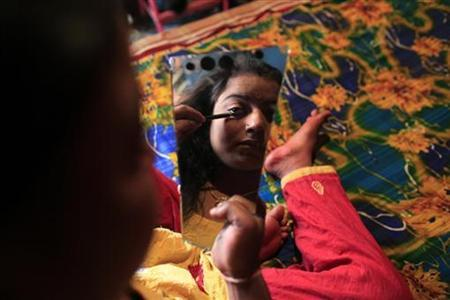 Seventeen-year-old prostitute Hashi applies her makeup as she prepares for customers at Kandapara brothel in Tangail, a northeastern city of Bangladesh, March 5, 2012. REUTERS/Andrew Biraj