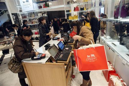 Shoppers wait in line to pay for purchases at a Macy's store in New York, November 23, 2012. REUTERS/Keith Bedford