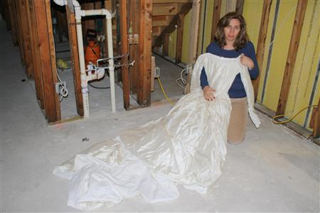 Cynthia Ramnarace poses with her damaged wedding dress in this handout photo courtesy of Sid Ramnarace which even though soaked and stained brown, she couldn't part with after Hurricane Sandy, at her home in Rockaway Beach, New York on December 1, 2012. REUTERS/Picture courtesy of Sid Ramnarace/Handout