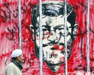 Homem caminha em frente a um mural ilustrando o presidente egípcio Mohamed Mursi, no Cairo. Três integrantes da equipe de conselheiros de Mursi, renunciaram em meio à crise provocada por um decreto que ampliou os poderes do mandatário, disseram fontes presidenciais nesta quarta-feira. 05/12/2012 REUTERS/Amr Abdallah Dalsh