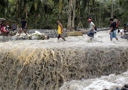 Residents carry the body of victim after flash floods brought by Typhoon Bopha swept New Bataan town in Compostela Valley in southern Philippines December 5, 2012. Blocked roads and severed communications in the southern Philippines frustrated rescuers on Wednesday as teams searched for hundreds of people missing after the strongest typhoon this year killed at least 283 people. REUTERS/Erik De Castro