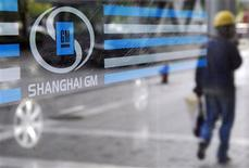 A labourer is reflected in the glass of a Shanghai General Motors exhibition hall in Shanghai in this May 28, 2009 file photo. REUTERS/Stringer/Files
