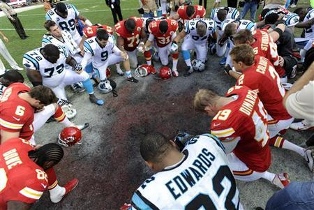 Kansas City Chiefs and Carolina Panthers players form a prayer circle after the Chiefs' win in a NFL football game in Kansas City, Missouri December 2, 2012. REUTERS/Dave Kaup