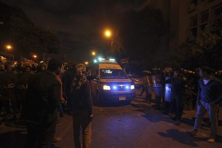 Anti-Mursi protesters and riot police open the road for an ambulance for injured protesters, during clashes with supporters of Egyptian President Mohammed Mursi, near the presidential palace in Cairo, December 5, 2012. REUTERS/Amr Abdallah Dalsh