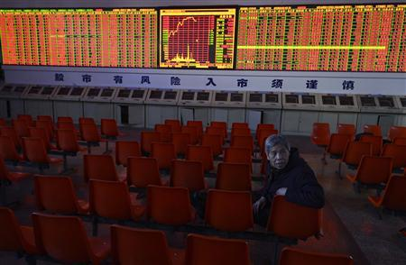 An investor chats with others in front of an electronic board showing stock information at a brokerage house in Taiyuan, Shanxi province, December 5, 2012. REUTERS/Stringer