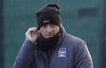Manchester City manager Roberto Mancini adjusts his hat as he watches his players during a training session at the club's Carrington training complex in Manchester, northern England December 3, 2012. REUTERS/Phil Noble