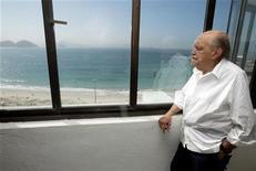 O arquiteto Oscar Niemeyer observa a praia de Copacabana desde seu escritório, após entrevista à Reuters, no Rio de Janeiro, em junho de 2003. Niemeyer morreu na quarta-feira aos 104 anos de infecção respiratória. 16/06/2003 REUTERS/Sergio Moraes