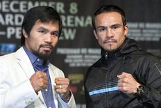 Filipino boxer Manny Pacquiao (L) and Juan Manuel Marquez of Mexico pose during a news conference at the MGM Grand in Las Vegas, Nevada December 5, 2012. Pacquiao and Marquez will fight for a fourth time in a welterweight bout at the MGM Grand Garden Arena on December 8. REUTERS/Las Vegas Sun/Steve Marcus