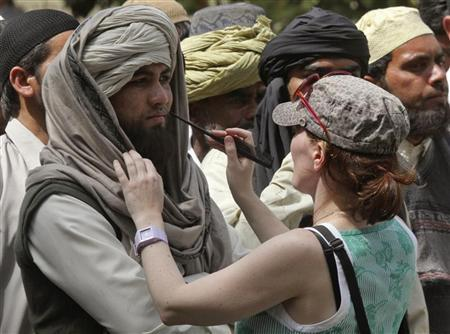 A crew member of Oscar-winning director Kathryn Bigelow's team for the movie ''Zero Dark Thirty'' applies makeup on an actor during a shoot at the filming location in the northern Indian city of Chandigarh March 17, 2012. REUTERS/Ajay Verma