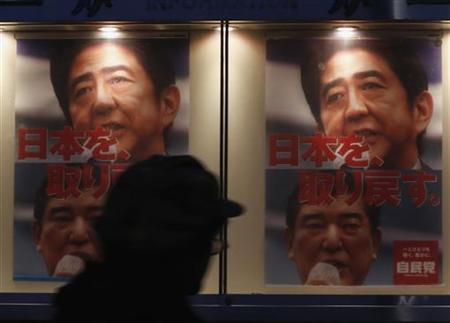 A man passes a poster of Japan's main opposition Liberal Democratic Party (LDP)'s poster bearing a photo of Shinzo Abe (top), the party's leader and former Prime Minister, displayed outside the LDP headquarters in Tokyo December 4, 2012. The characters on the poster reads, ''Recover Japan.'' REUTERS/Yuriko Nakao/Files