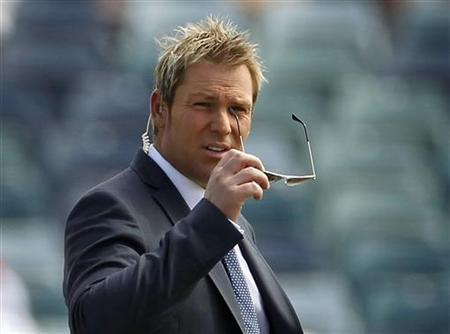 Former Australian bowler, Shane Warne, removes his glasses as he carries out his duty as a television commentator on the WACA ground in Perth December 16, 2010, ahead of the first day's play of third Ashes test between Australia and England. REUTERS/Tim Wimborne/Files