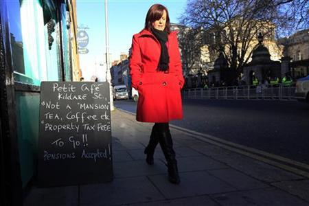 A woman walks past a sandwich board commenting on the Irish Budget, outside a coffee shop in Dublin December 5, 2012. The Irish government will test the economy and the public's patience with another 3.5 billion euro dose of austerity on Wednesday, though better service sector and jobless data will help soften the blow. REUTERS/Cathal McNaughton (IRELAND - Tags: POLITICS FOOD BUSINESS)