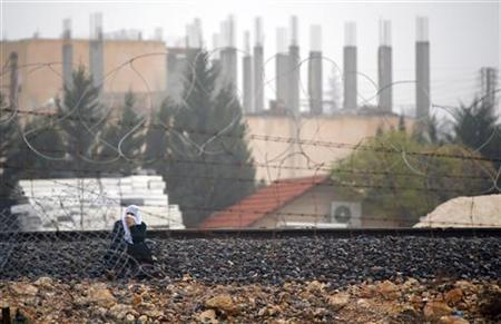 A Syrian woman sits at a railway track as she tries to cross the border from the Syrian town of Ras al-Ain to the Turkish border town of Ceylanpinar, Sanliurfa province December 4, 2012. REUTERS/Laszlo Balogh (TURKEY - Tags: MILITARY POLITICS CONFLICT)