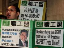 "A labour union representative chants slogans while carrying a sign with a portrait of Singapore's Prime Minister Lee Hsien Loong during a protest outside the Singapore Consulate in Hong Kong December 5, 2012. The group demanded for the release of a Chinese immigrant bus driver being sentenced to jail in Singapore after a protest in late November. The sign reads, ""Singapore Prime Minister Lee Hsien Loong. Release striking bus driver! Withdraw charges! Stop deporting! Protect workers rights to protest!"" REUTERS/Bobby Yip"