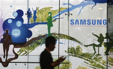 A man using a mobile phone walks past a Samsung Electronics' advertisement in Seoul October 5, 2012. REUTERS/Kim Hong-Ji