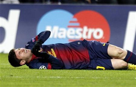 Barcelona's Lionel Messi reacts after picking up an injury while trying to score a goal against Benfica's goalkeeper Artur during their Champions League Group G soccer match at the Nou Camp stadium in Barcelona December 5, 2012. REUTERS/Gustau Nacarino