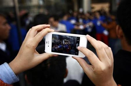 A woman takes a photograph using her iPhone of members of the public entering a new Apple store during the official opening in Beijing's Wangfujing shopping district October 20, 2012. REUTERS/David Gray/Files