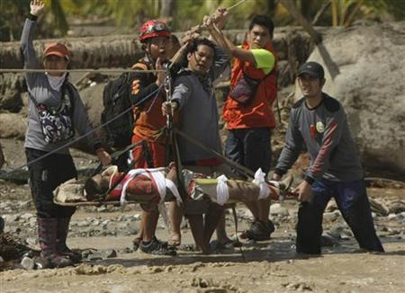 Rescuers evacuate Carlos Agang after he was found alive and survived flooding after Typhoon Bopha in New Bataan town in Compostela Valley in southern Philippines December 6, 2012. REUTERS/Stringer