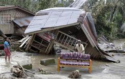"""Жители Компостелы чистят диван у полуразрушенного тайфуном """"Бофу"""" дома 5 декабря 2012 года. Мощнейший тайфун, прокатившийся в начале недели по Филиппинам, унес жизни 332 человек, и спасатели продолжают поиски сотен пропавших без вести людей. REUTERS/Erik De Castro"""