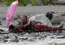 Mulher grávida que sobreviveu a enchente segura seu filho na maca, enquanto é resgatada na cidade de New Bataan, em Compostela Valley, sul das Filipinas. 6/12/2012 REUTERS/Erik De Castro