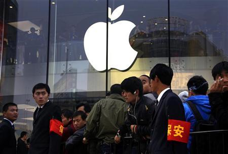 Security staff watch over a crowd gathered for the opening of a new Apple store in Beijing's Wangfujing shopping district October 20, 2012. REUTERS/David Gray