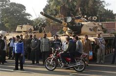 Apoiadores da Irmandade Muçulmana ficam perto de tanques em posição do lado de fora do palácio presidencial egípcio, no Cairo. 6/12/2012 REUTERS/Asmaa Waguih
