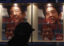 Мужчина проходит мимо плаката с изображением лидера Либерально-демократической партии Синдзо Абэ (сверху) в Токио 4 декабря 2012 года. Консервативная Либерально-демократическая партия Японии, скорее всего, победит на парламентских выборах 16 декабря 2012 года с существенным большинством голосов, свидетельствуют данные медиа-опросов. REUTERS/Yuriko Nakao