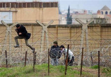 A Syrian man jumps over barbed wire as he tries to cross the border from the Syrian town of Ras al-Ain to the Turkish border town of Ceylanpinar, Sanliurfa province, December 6, 2012. REUTERS/Laszlo Balogh