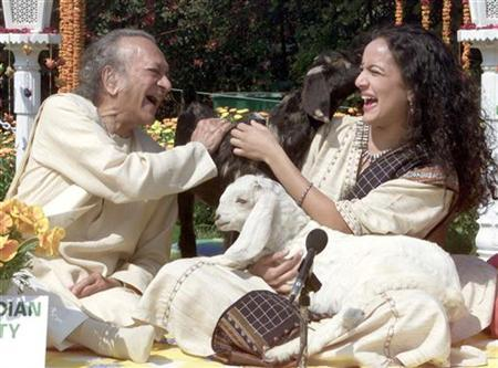 Sitar maestro Pundit Ravi Shankar laughs with his daughter sitar player Anoushka Shankar as they sit beside sheep in New Delhi February 25, 2002. REUTERS/Pawel Kopczynski/Files