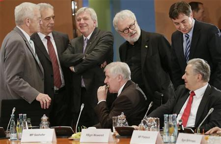 Bavarian federal state premier Horst Seehofer is surrounded by colleagues as he eats a piece of Christmas cake before a meeting of federal state prime ministers with Chancellor Angela Merkel in Berlin December 6, 2012. REUTERS/Tobias Schwarz