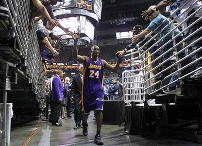 Los Angeles Lakers shooting guard Kobe Bryant (24) high fives fans as he leaves the court after their NBA basketball game against the New Orleans Hornets in New Orleans, Louisiana December 5, 2012. REUTERS/Jonathan Bachman